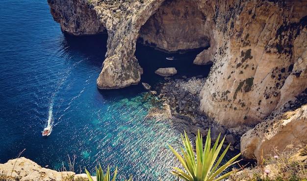 Vue de la grotte bleue et petits bateaux avec des touristes