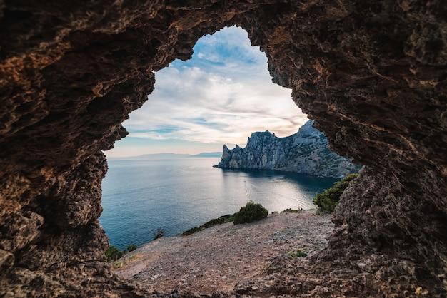 Vue de la grotte rocheuse à la baie de la mer au coucher du soleil