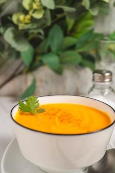 Vue hachée d'un bol blanc avec une soupe de crème de courge et de carottes