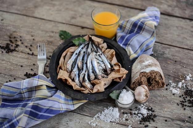 Vue d'en haut sur les anchois frais sur une assiette sur du papier sulfurisé avec du jus d'orange frais, de l'ail, du pain, du sel et du poivre autour de la serviette bleue près de la fourchette sur la table en bois