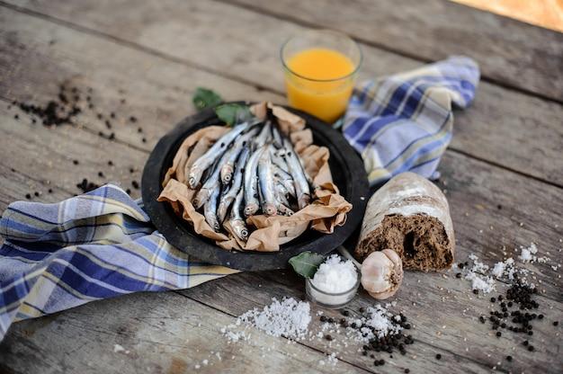 Vue d'en haut sur les anchois frais sur une assiette sur du papier sulfurisé avec du jus d'orange frais, de l'ail, du pain, du sel et du poivre autour de la serviette bleue sur la table en bois