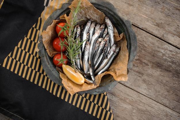 Vue d'en haut sur les anchois frais sur l'assiette avec un romarin, des tomates cerises et du citron sur la table en bois et une serviette noire et jaune
