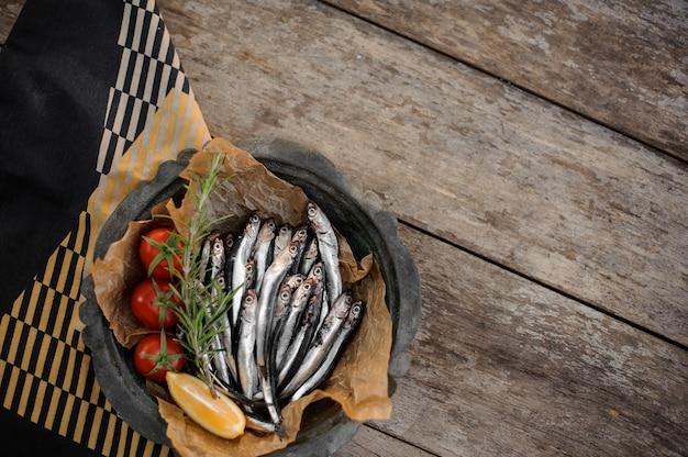 Vue d'en haut sur les anchois frais sur l'assiette avec un romarin, des tomates cerises et du citron sur la table en bois et une serviette rayée noire, blanche et jaune