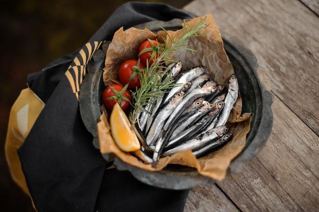 Vue d'en haut sur les anchois frais sur l'assiette avec un romarin, des tomates cerises et du citron sur la table en bois et une serviette rayée noire et jaune