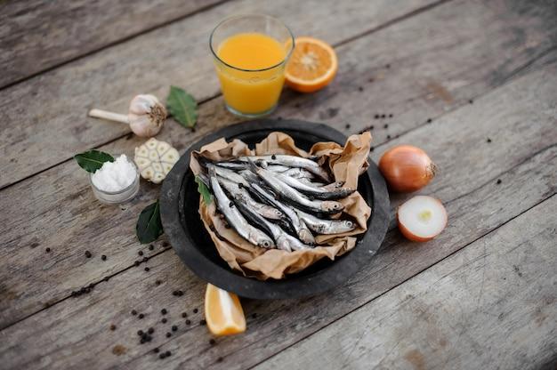 Vue d'en haut sur les anchois frais sur une plaque sur du papier sulfurisé avec du jus d'orange frais, de l'ail, de l'oignon et du citron autour de la table en bois
