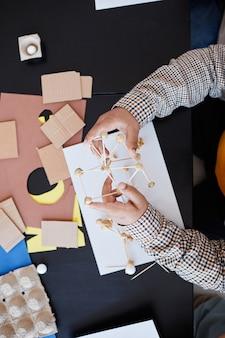 Vue de haut en bas sur un enfant méconnaissable fabriquant des modèles en carton pendant un cours d'art et d'artisanat à l'école avec une enseignante, espace de copie