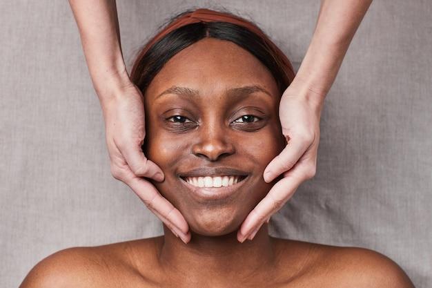 Vue de haut en bas sur une femme afro-américaine souriante profitant d'un massage du visage et regardant la caméra