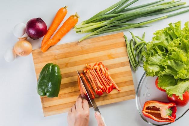 Vue de haut en bas sur une planche à découper, les mains coupant et tranchant les légumes.