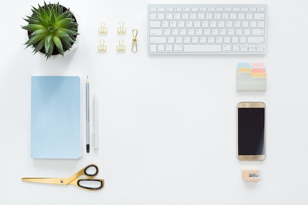 Vue d'en haut du lieu de travail avec clavier d'ordinateur, ordinateur portable, fleur en pot verte et téléphone portable, poser à plat.