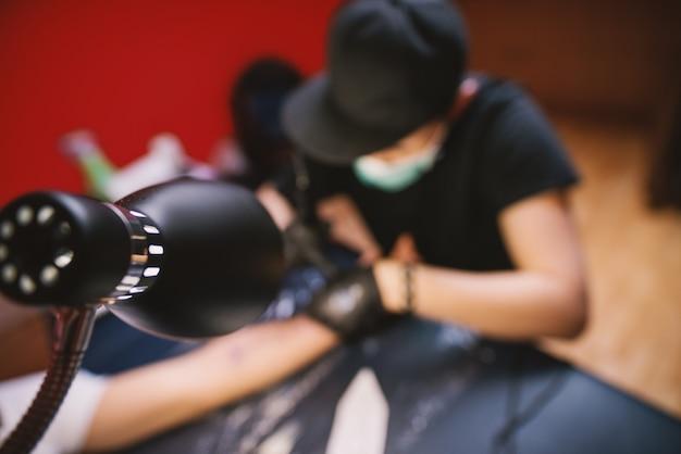 Vue d'en haut du tatoueur encrant le bras des clients dans sa boutique.