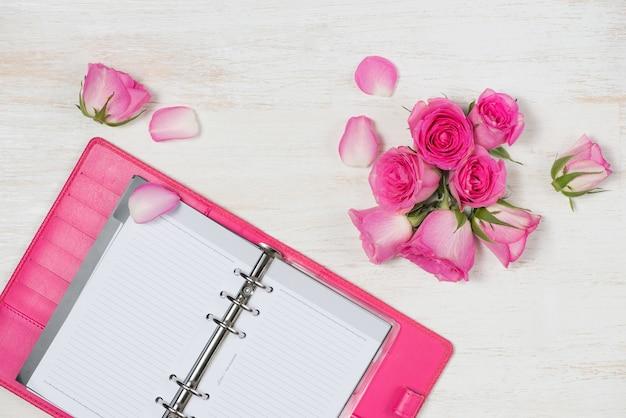 Vue d'en haut avec des fleurs roses et un cahier. table en bois blanc.