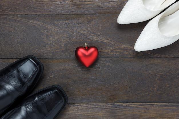 Vue en haut de la forme du coeur avec des chaussures pour hommes et des chaussures pour femmes sur fond en bois.