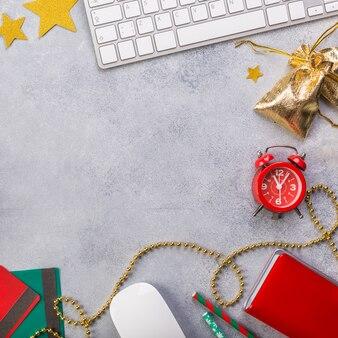 Vue d'en haut avec horloge rouge, carnet bleu, clavier, présente dans le panier, cartes de crédit.
