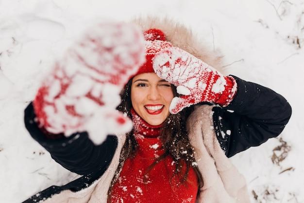 Vue d'en haut sur jeune femme heureuse souriante assez candide dans des mitaines rouges et bonnet tricoté portant un manteau noir couché dans la neige dans le parc, des vêtements chauds, s'amuser