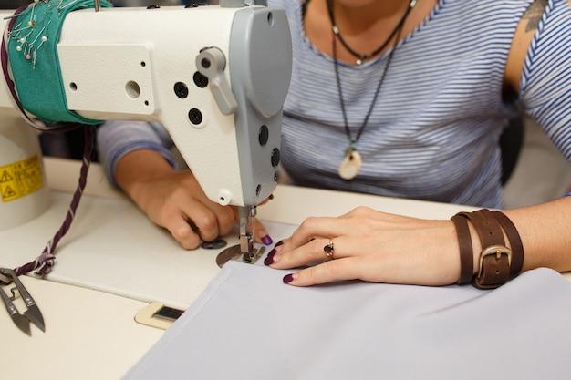 Vue d'en haut sur les mains du tailleur féminin travaillant sur la machine à coudre. industrie de la fabrication de vêtements