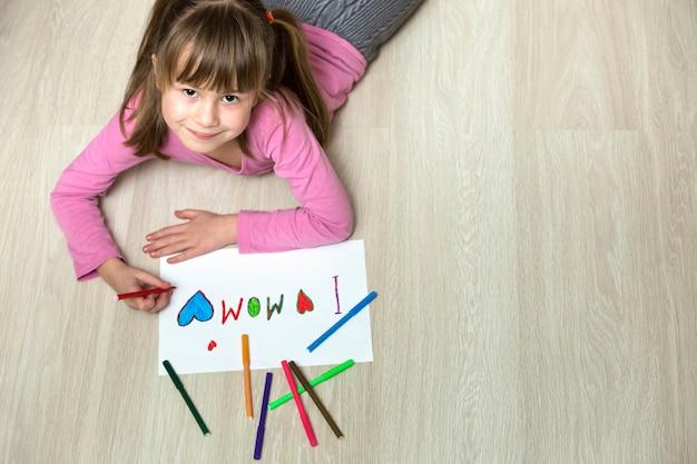 Vue d'en haut de mignon enfant fille dessin avec des crayons de couleur j'aime maman sur papier blanc. éducation artistique, concept de créativité.