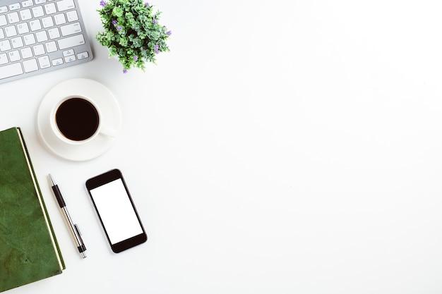 Vue d'en haut. ordinateur portable, stylo, ordinateur portable, smartphone et tasse de café sur un bureau blanc