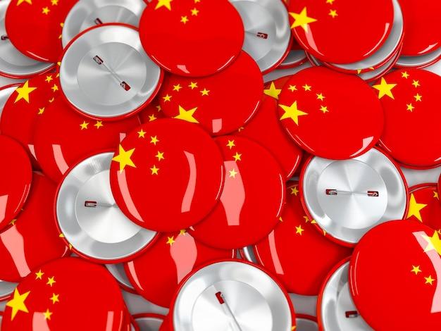 Vue d'en haut sur une pile de badges bouton avec le drapeau de la chine. rendu 3d réaliste