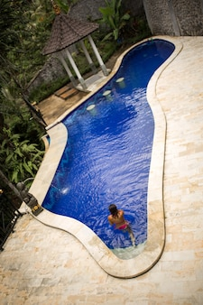 Vue d'en haut sur sexy fille en maillot de bain rose se détendre et bronzer au swimpool