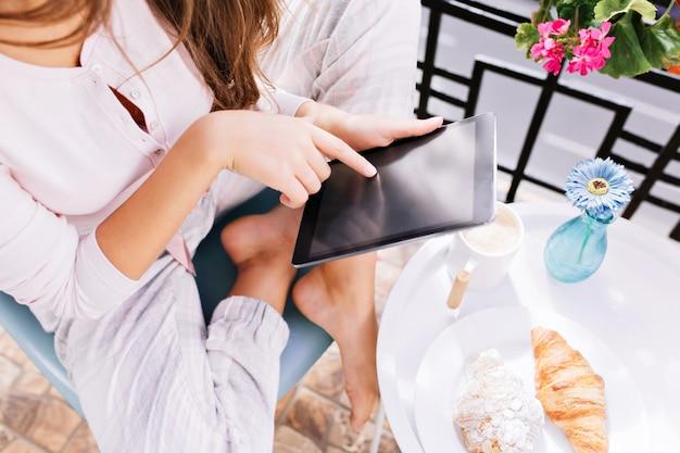 Vue d'en haut de la tablette dans les mains d'une jeune fille en pyjama assis sur un balcon, prenant son petit déjeuner.