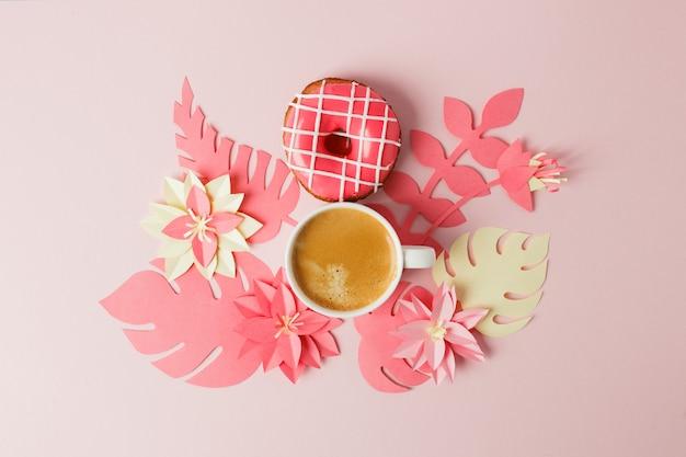 Vue d'en haut avec une tasse de café, un beignet et des fleurs en papier de fabrication artisanale d'origami moderne