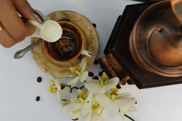 Vue d'en haut sur la tasse de café dans laquelle verser du lait sur le tableau blanc