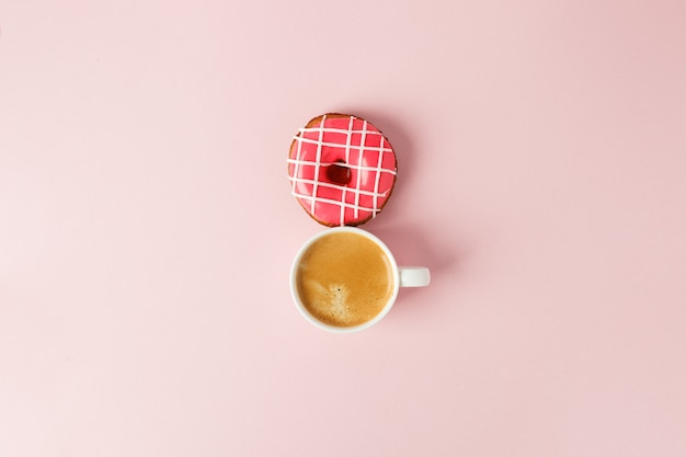 Vue d'en haut avec une tasse de café et un espace de copie de beignet rose.