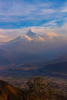 Vue sur une haute montagne aux cimes enneigées et une ville installée à ses pieds