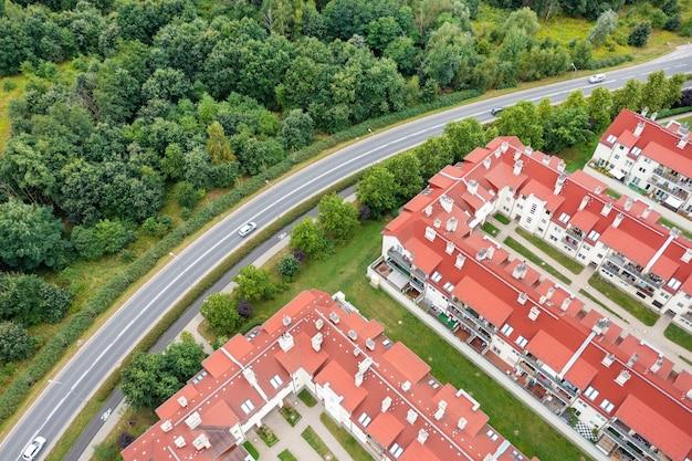 Vue d'une hauteur des maisons rouges et à côté de la forêt avec la route, paysage d'été, drone