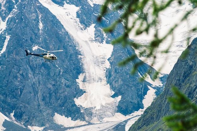 Vue d'hélicoptère à travers les branches d'arbres sur fond de mur enneigé géant