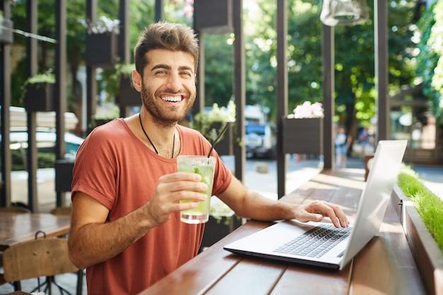Vue d'heureux homme barbu caucasien utilisant un ordinateur portable souriant avec des dents, surfant sur internet assis à table en bois à la cafétéria d'été et boire de la limonade.