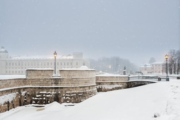Vue d'hiver urbain de l'ancienne ville russe de gatchina. le vieux palais en hiver est illuminé le soir.