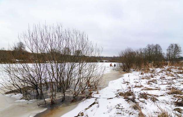 Vue hivernale de la petite rivière gelée en russie et des pêcheurs sur glace