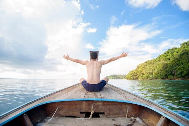 Vue de l'homme en maillot de bain profitant du bateau sur la belle montagne et l'océan