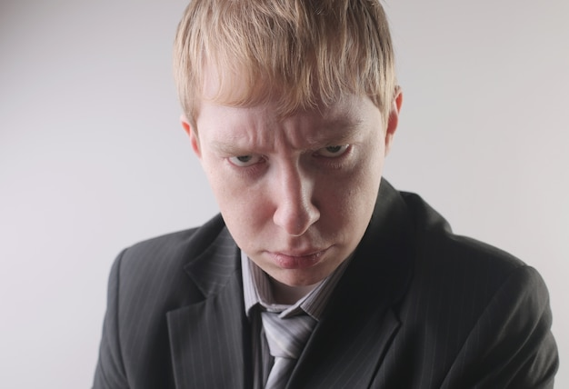 Vue d'un homme portant un costume de couleur foncée avec une expression faciale en colère - concept: en colère