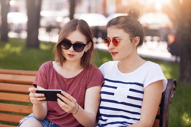 Vue horizontale d'adolescentes dans les tons regarder la vidéo du didacticiel en ligne via un téléphone portable, connecté à internet sans fil, poser sur un banc, profiter des loisirs et du jour de congé, avoir de bonnes relations