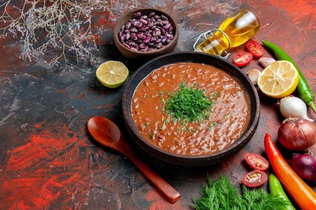 Vue horizontale de la bouteille d'huile de soupe aux tomates haricots citron et un bouquet de vert sur table de couleurs mixtes