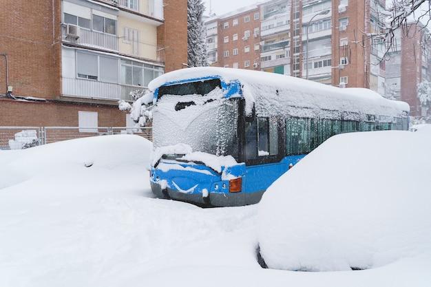 Vue horizontale d'un bus public endommagé à cause d'une tempête de neige à madrid.