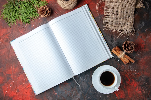Vue horizontale d'un cahier à spirale non écrit ouvert et de cônes de conifères et d'une branche de sapin une tasse de thé noir à la cannelle et aux citrons verts sur fond sombre