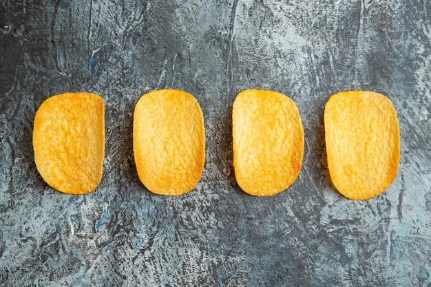 Vue horizontale de chips cuites au four croquantes alignées dans une rangée sur tableau gris