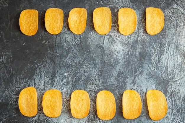 Vue horizontale de crunchy cuit cinq chips alignés sur table grise photo