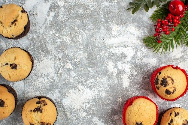 Vue horizontale de délicieux petits gâteaux avec des branches de chocolat et de sapin sur la surface de la glace
