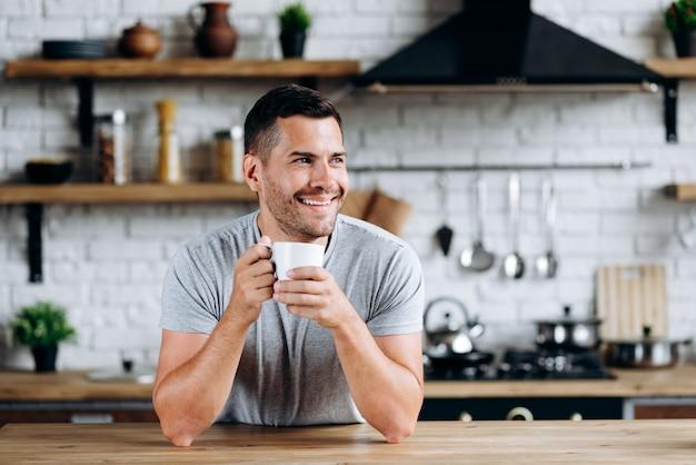 Vue horizontale du bel homme assis sur la chaise s'appuya sur la table, souriant et détournant les yeux tout en buvant du café. image à la cuisine confortable