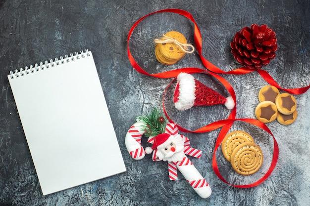 Vue horizontale du cahier et du chapeau de père noël et des biscuits-cadeaux de cône de conifère rouge chocolat cornel sur une surface sombre