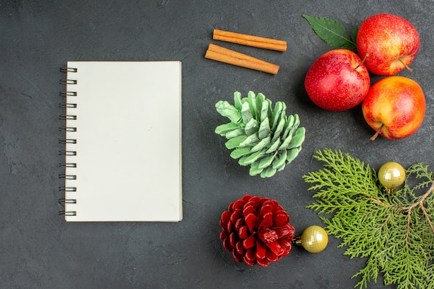 Vue horizontale du cahier et des pommes fraîches, des citrons verts à la cannelle et des accessoires de décoration sur fond noir