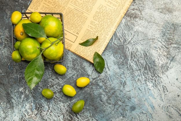 Vue horizontale du panier noir avec des mandarines vertes fraîches et des kumquats sur des journaux sur fond gris image stock
