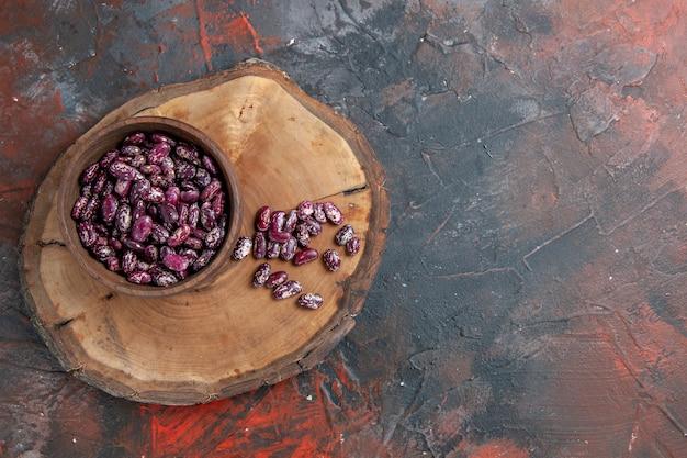 Vue horizontale du pot instantané de haricots noirs dans un bol brun sur un plateau en bois sur table de couleurs mixtes