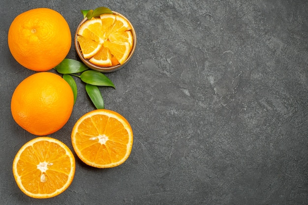 Vue horizontale de l'ensemble d'oranges jaunes entières et hachées sur table sombre