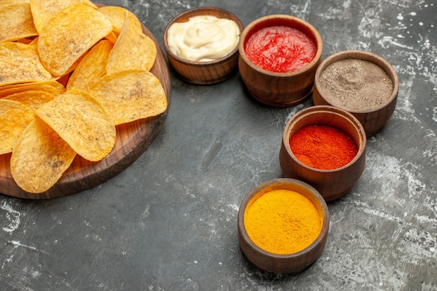 Vue horizontale d'épices croustilles et mayonnaise avec du ketchup sur tableau gris