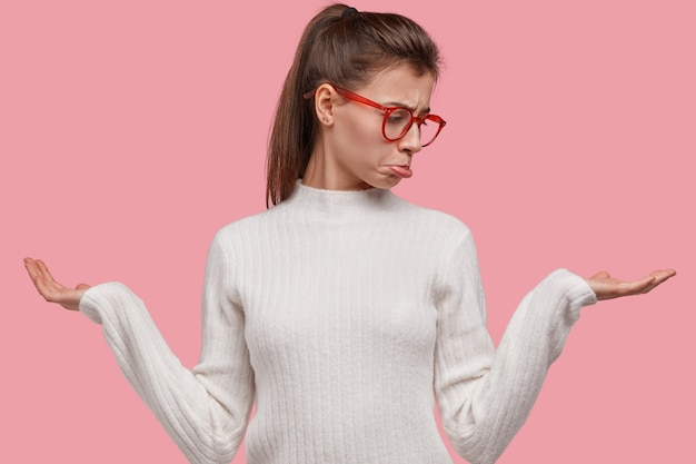 Vue horizontale de la femme indifférente hésitante bouleversé la lèvre de sacs à main, soulève les paumes, a la queue de cheval, expression indécise, porte des lunettes